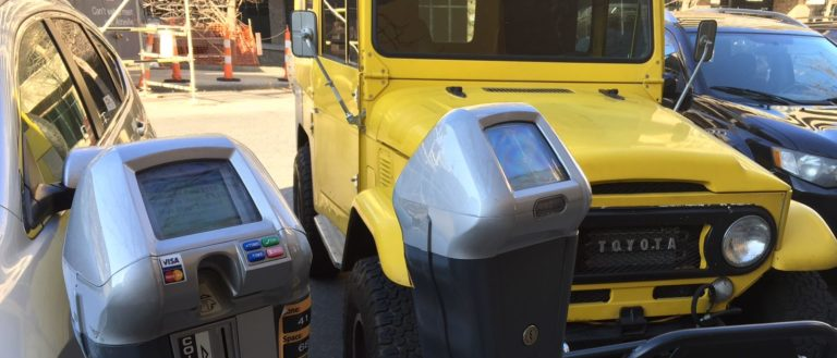 A yellow jeep parking on the street in Asheville.