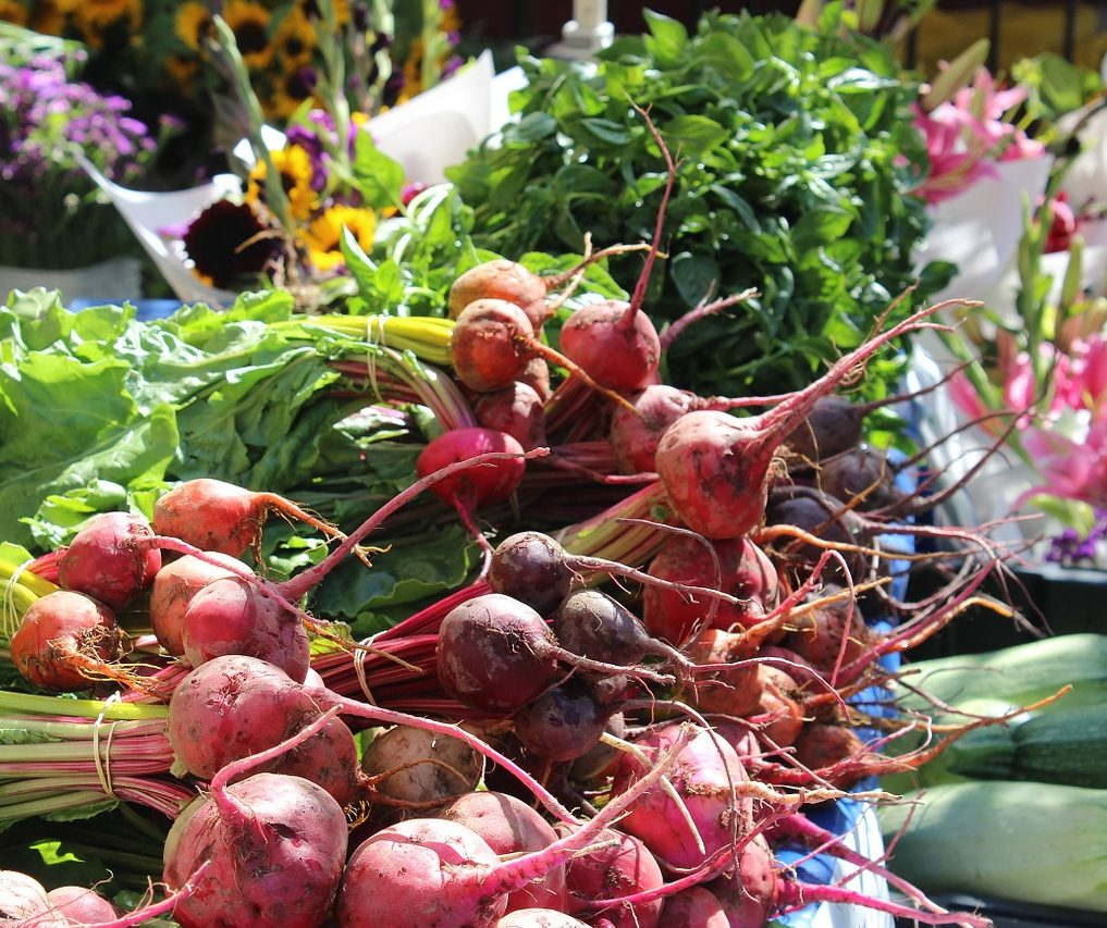 Beets and greens on a farmers market table.