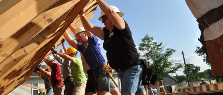 Habitat for Humanity volunteers standing up a wall.
