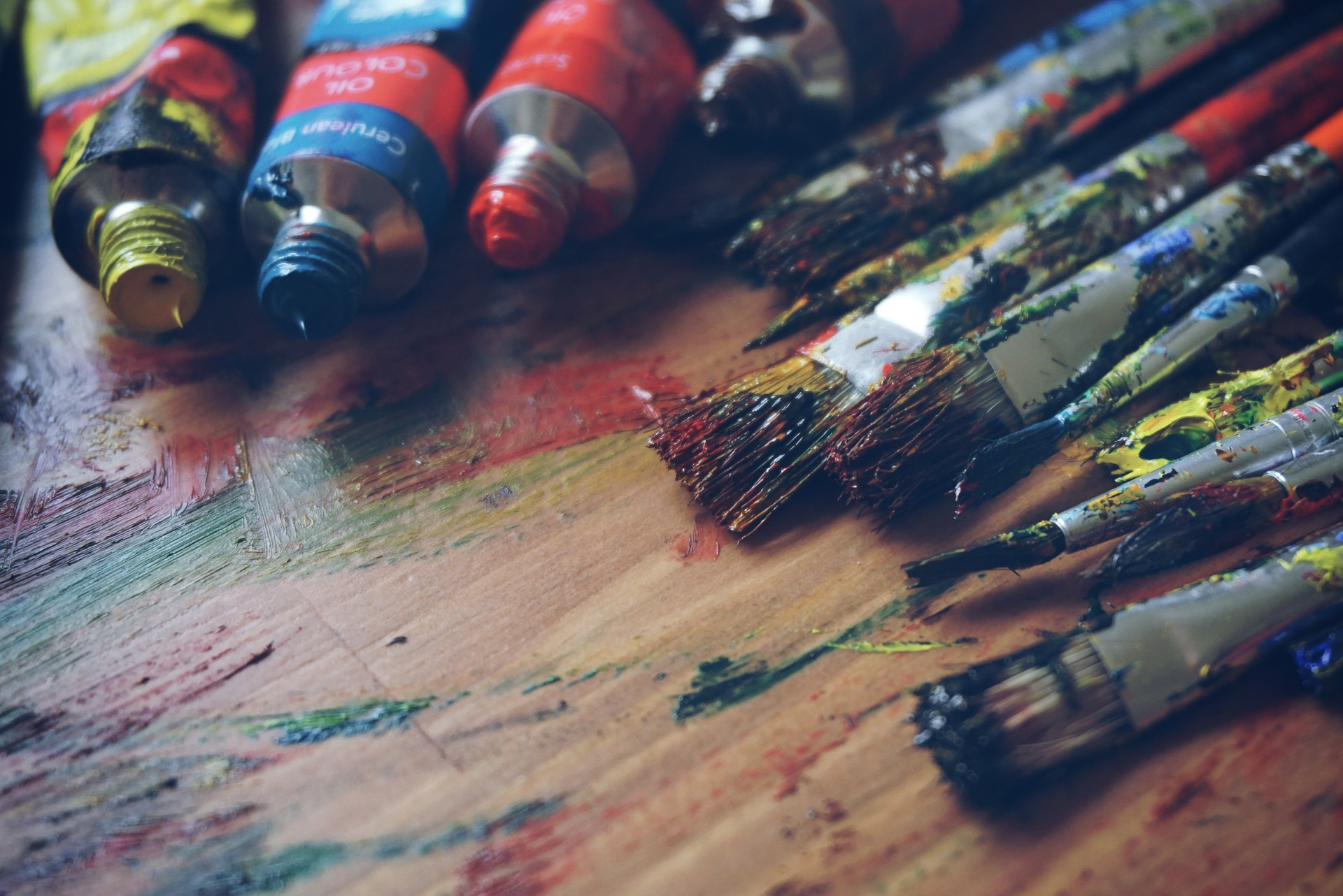 Paint and paint brushes on an art board.