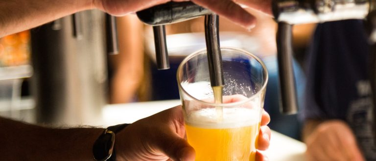 A bartender pouring a glass of beer from tap.