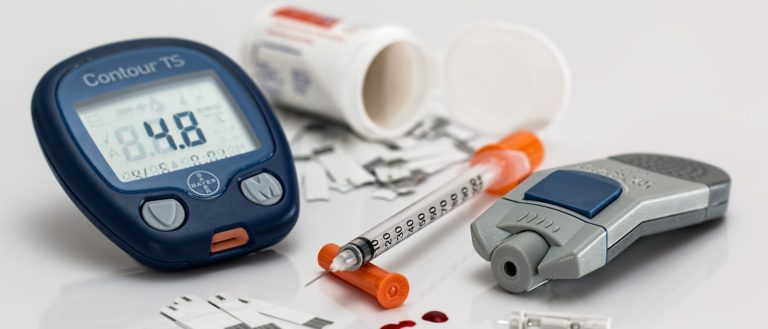 Diabetic medications and tools on a table.