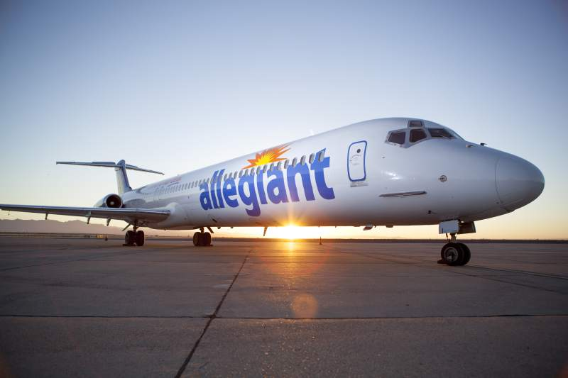 An Allegiant Air airplane on a tarmac with the sun in the background.