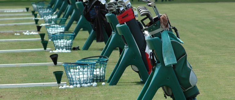 A row of golf bags lined up at the driving range.