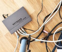 A Netgear internet router on the floor hooked up to several cables.