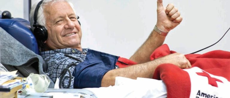 An older gentleman donating blood with the Red Cross.