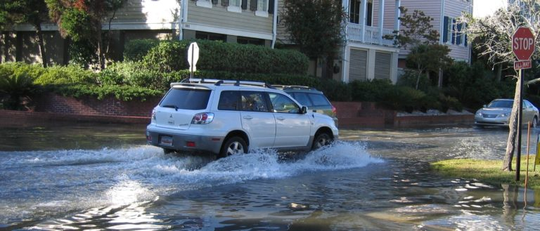 A vehicle driving through a flooded street.