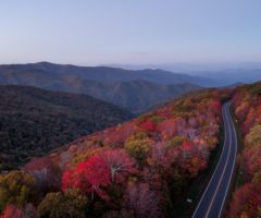 A road winding its way through the changing fall foliage.