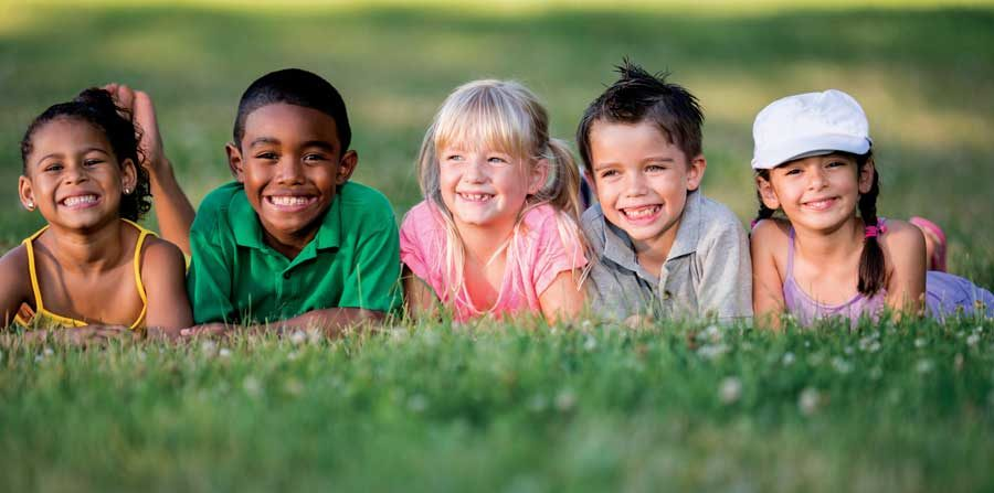 A group of smiling children lying on grass.