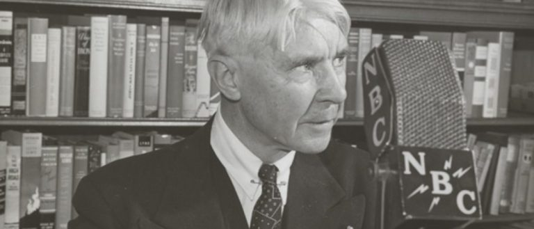 Carl Sandburg speaking at a podium into a microphone.