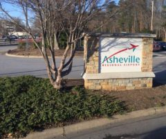 A sign on the side of the road for Asheville Airport.