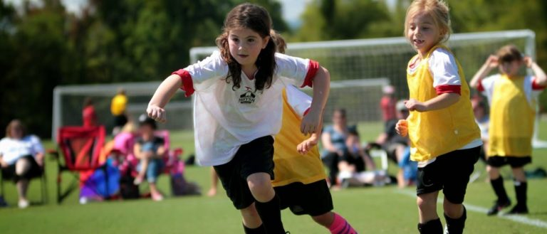 A girl chasing a soccer ball at JBL Soccer Complex.