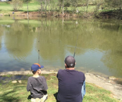 A child and parent fishing on the lakeside.