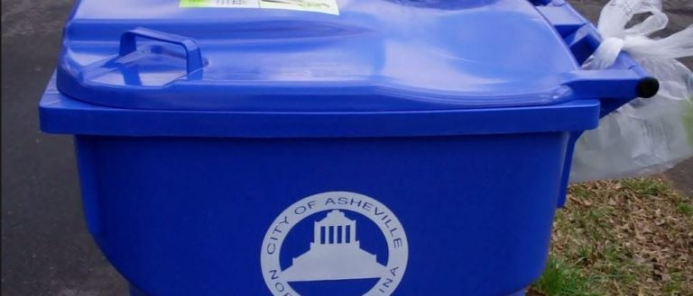 A blue City of Asheville recyclin bin on the curb.