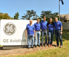 GE Aviation workers in front of their campus's sign.