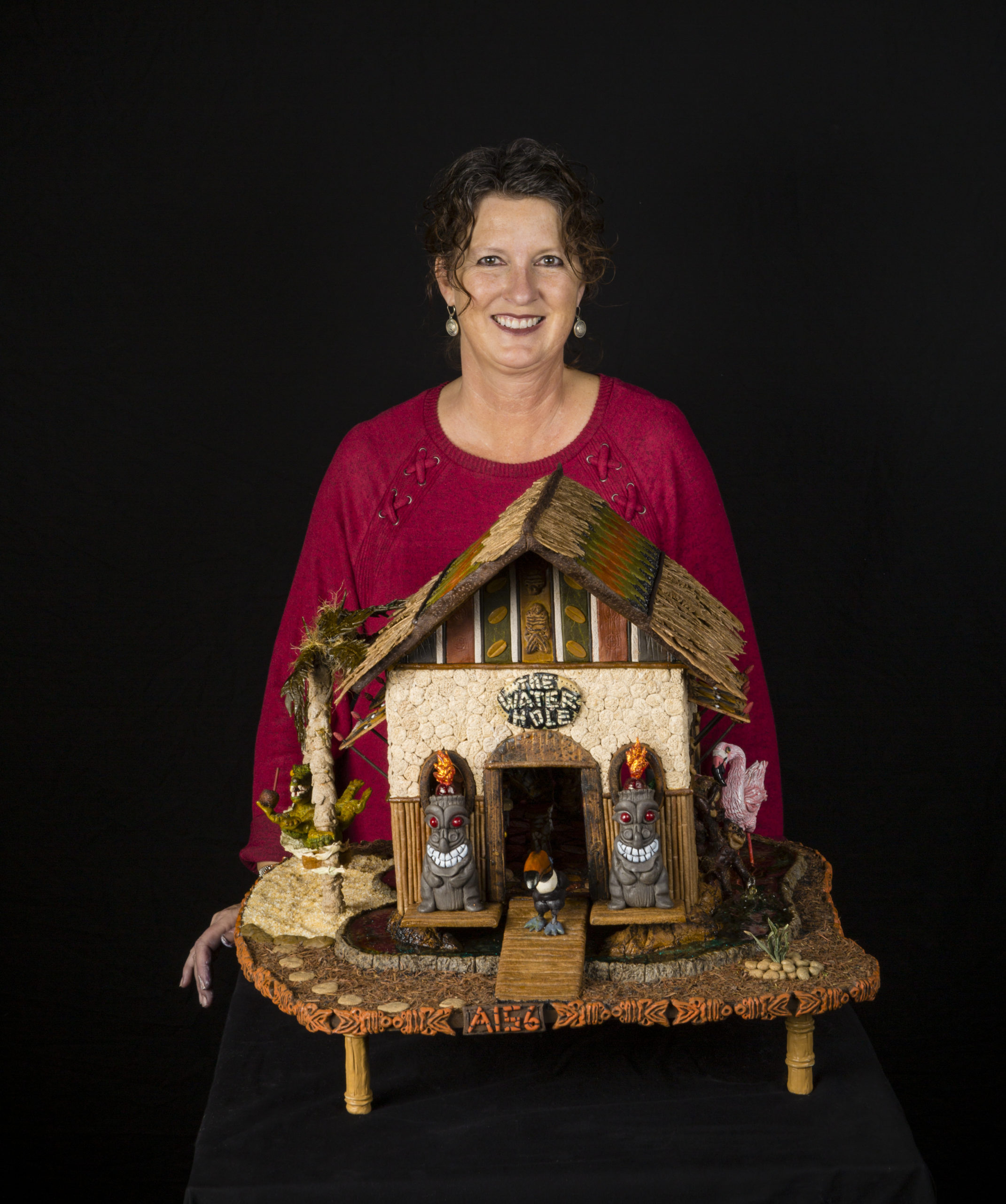 Gail Oliver holding a decorated gingerbread cabin.
