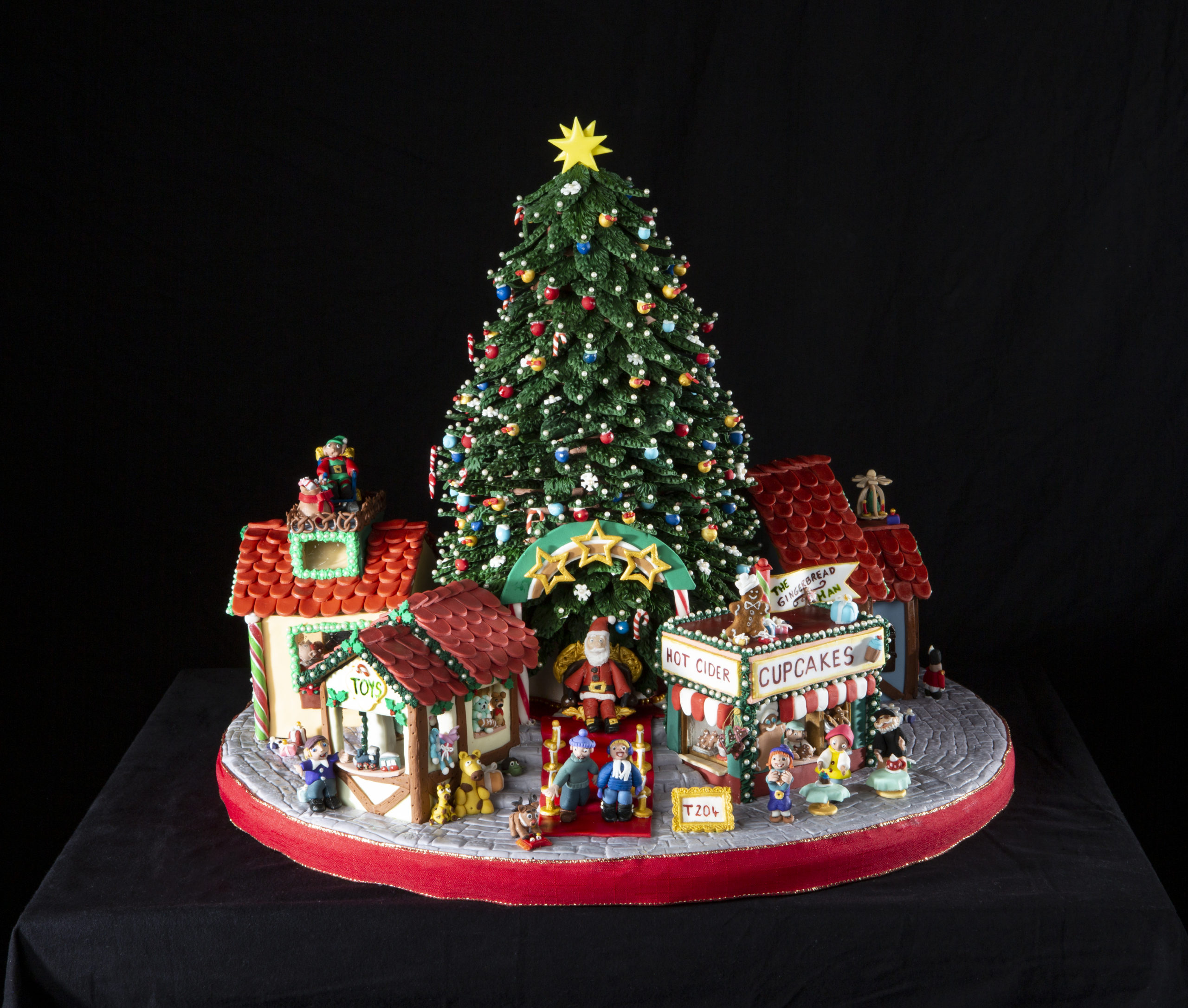 A gingerbread display with a Christmas tree and several buildings.