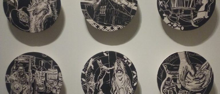 Six decorated black plates in an art museum.