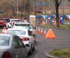 A row of cars waiting to enter a drive-through clinic.