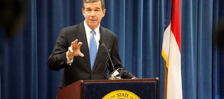 Governor Cooper speaking at a podium.