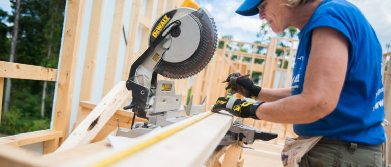 A volunteer cutting wood on a home construction site.