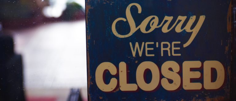 A closed sign on the door of a business.
