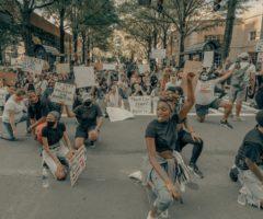 Protestors against police violence kneeling on a street.