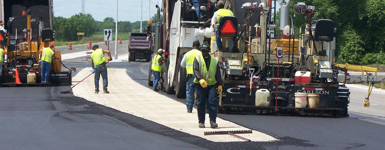 Workers resurfacing a two lanes of road.