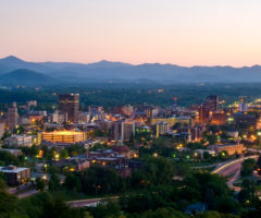 Downtown Asheville lit up at dusk.