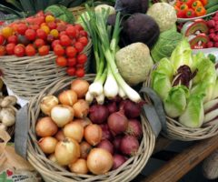 A variety of fruits and vegetables in baskets on a table.