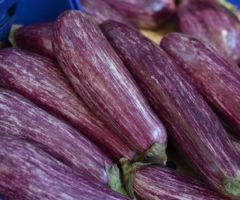 A bundle of purple eggplants on a table.