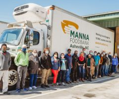 Masked volunteers in front of a food bank truck.