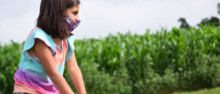 A child wearing a mask at a corn maze.