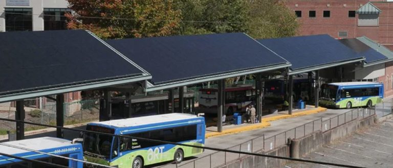 Buses parked under solar panel-covered awnings.