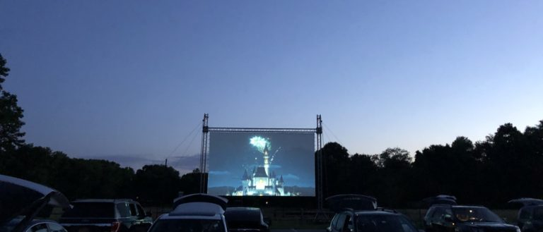 Cars in a parking lot facing a projected screen.