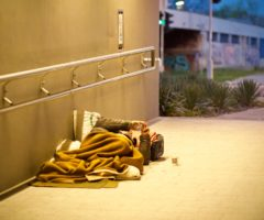 A person sleeping outside a building.