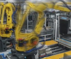 Robotic arms in motion on a manufacturing floor.