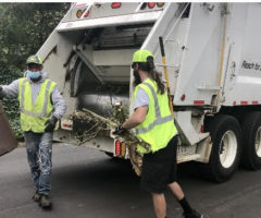 Two people in vests loading a garbage truck.