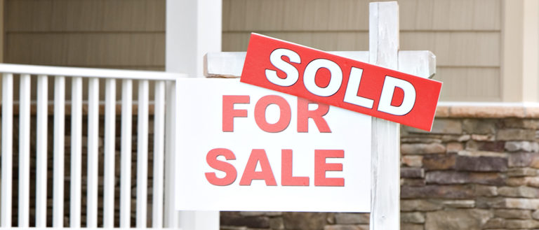 A for sale sign in front of a home.
