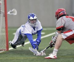 A lacrosse goalie attempting to block a shot.