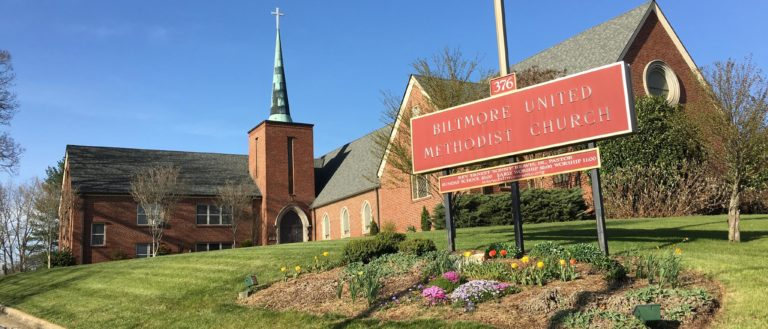 A red brick church next to a road.