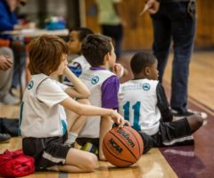Young basketball players sitting down listening to a coach.