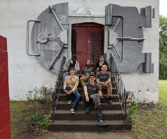 A group of artists sitting in front of a safe in front of a door.