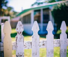 A white picket fence in front of a house.