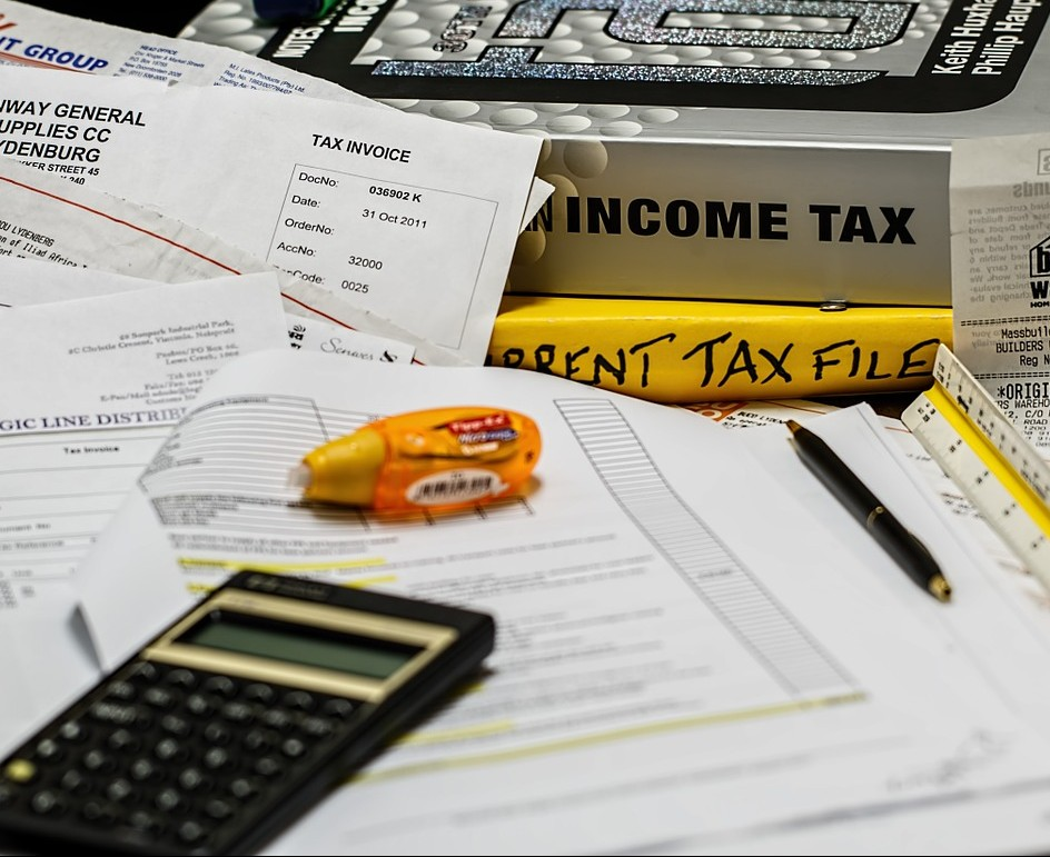 Tax documents and a calculator on a table.
