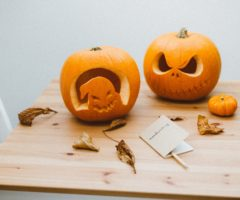 Two freshly carved pumpkins on a wooden table.
