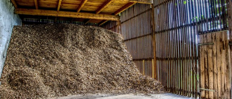 An outdoor building filled with mulch.