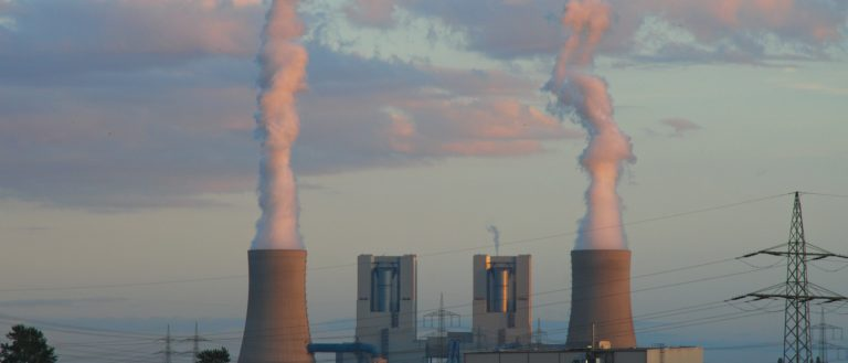 An operating coal power plant in the distance.