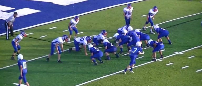 Brevard High School football players lining up against another team.