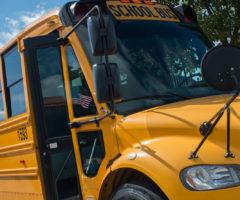 An empty school bus in front of a school.